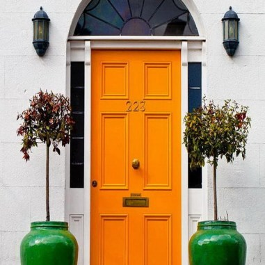 Orange is a powerful and fun color for an entry. How wonderful is it with these green glazed pots?! via boombety