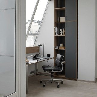Home Office in Contemporary Loft Nook, Slanted large window encased with tall gray and white bookcase and covered closed tall storage cabinet, chair on roller wheels at desk