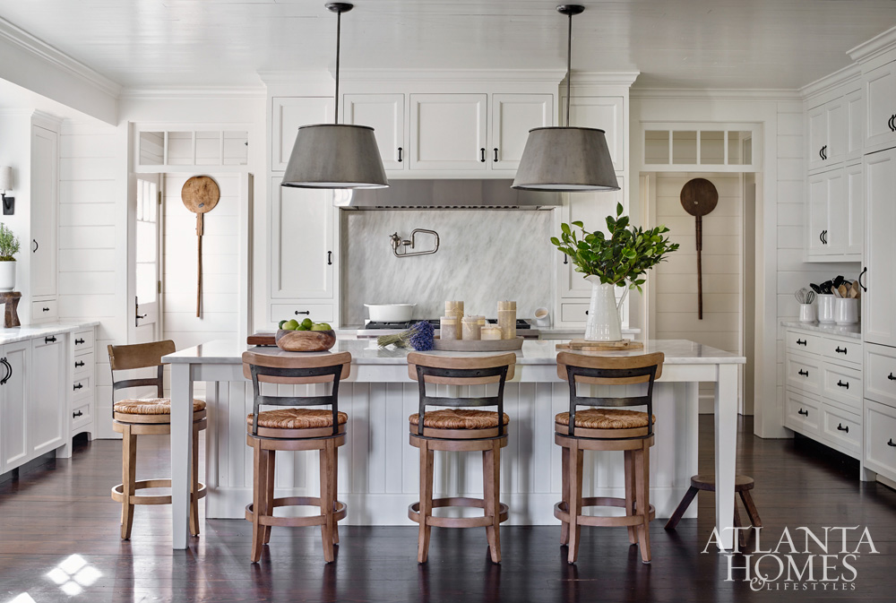 Traditional white kitchen with large island with light wood woven seat counter stools, pair of silk shaded hanging lights, wood flooring and white ship lap walls