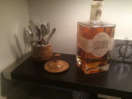 littleblackdomicile.com photo of ikea EBKY shelf with bourbon bottle and mustard colored ceramic pot full of spoons