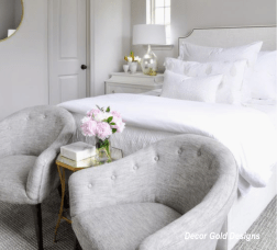Guest bedroom with pair of chairs at foot of white upholstered bed, vase of pink peony's-decor gold designs