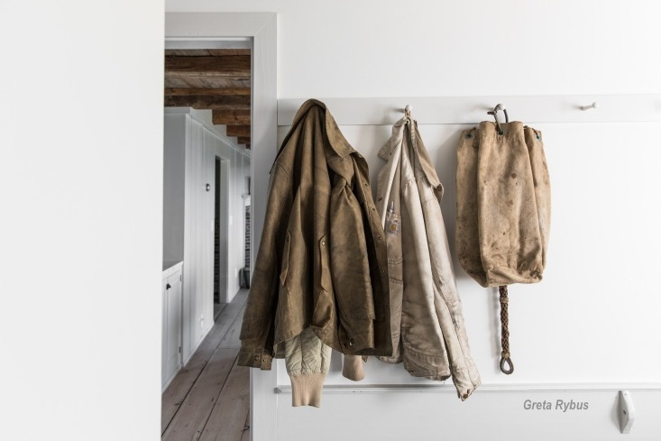 greta rybus, worn leather jackets and bag hanging on a simple white peg board in a maine seaside cottage