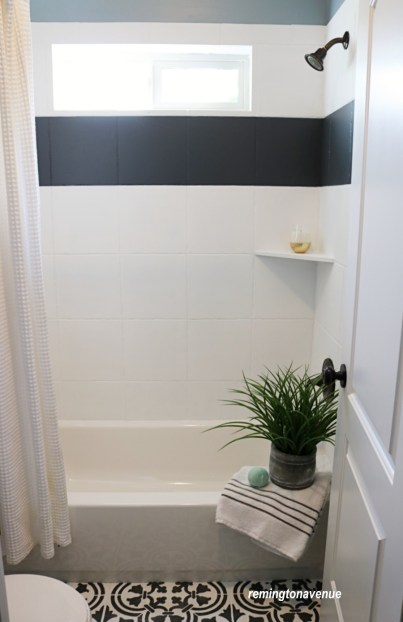 A standard bath transformed to the Zen spa of our dreams. Black and white patterned floor tile and a bold black stripe in the shower wall tile. -remingtonavenue