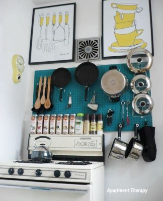 kitchen pegboard painted deep aqua color with wooden spoons, pots, lids, oven mit
