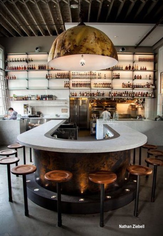 nathan ziebell photo of a bar with huge metal pendant light, wood round bar stools, bottles on shelf