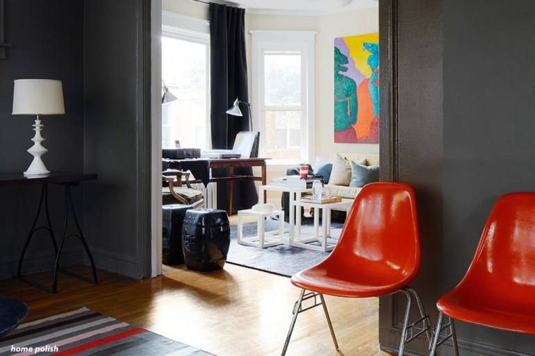 Homepolish-interior-design-red chairs-colorful large art-white walls- black walls -wood floors