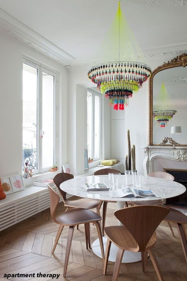 apartment therapy living room- colorful chandelier-antique mirror- marble fireplace- herringbone floor-white walls