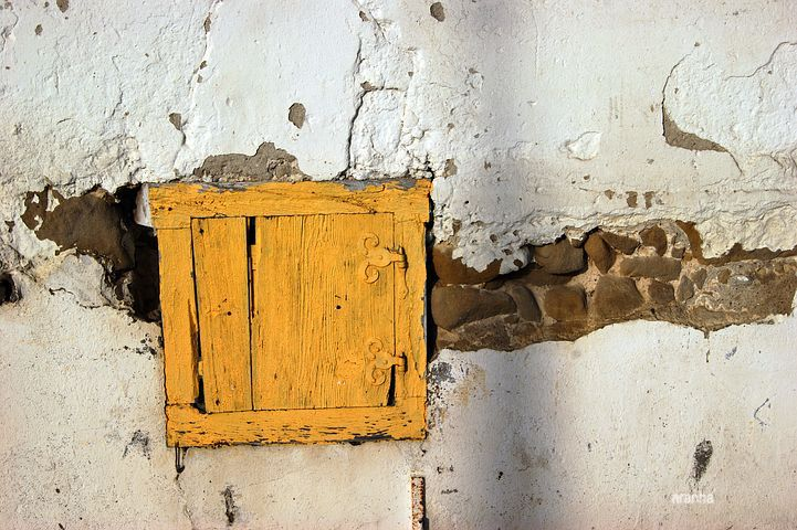 aranah old small yellow door in brick plastered wall