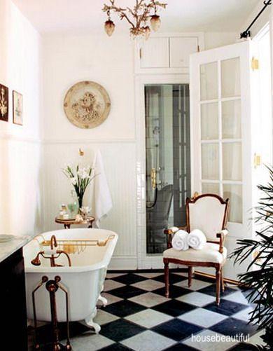 house beautiful- vintage bathroom-black and white checkerboard floor- clawfoot tub-brass chandelier
