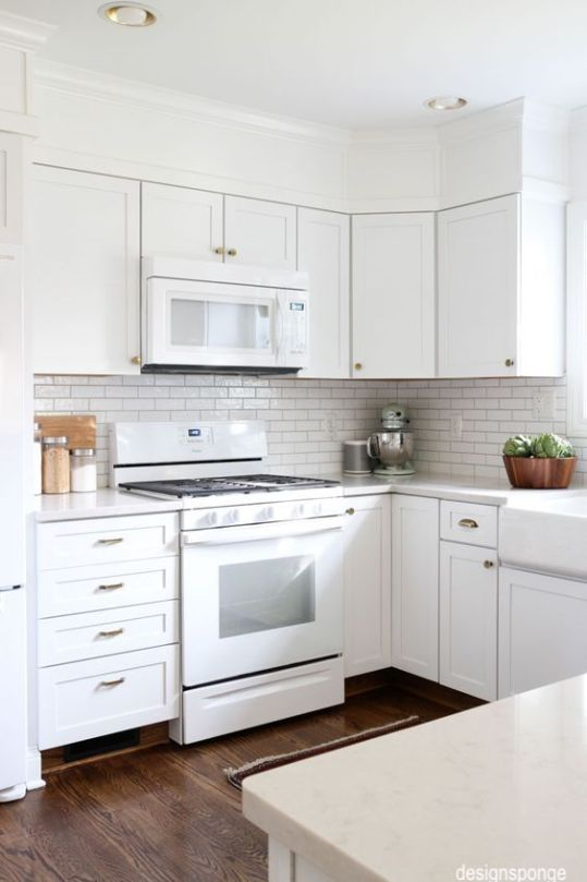 designsponge-white-cabinets-gas-range-microwave