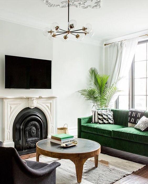 pinterest-green-velvet-sofa-white-walls-metal-fireplace-palm-plants