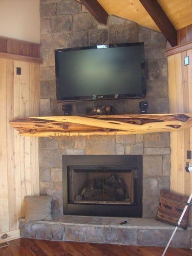 Juniper log fireplace mantel on a corner stone fireplace.