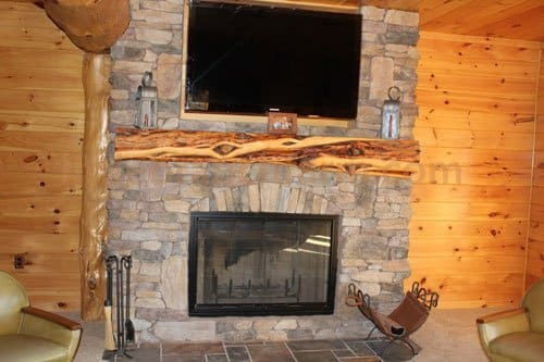 Juniper log fireplace mantel and stone fireplace
