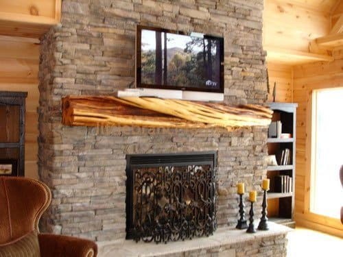 Juniper fireplace mantel on a stacked stone fireplace.