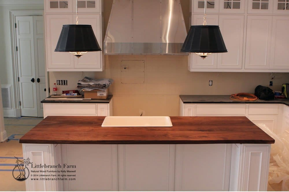Butcher block island countertop on white cabinets.