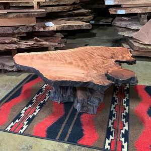 Live edge wood rustic coffee table on a rug.