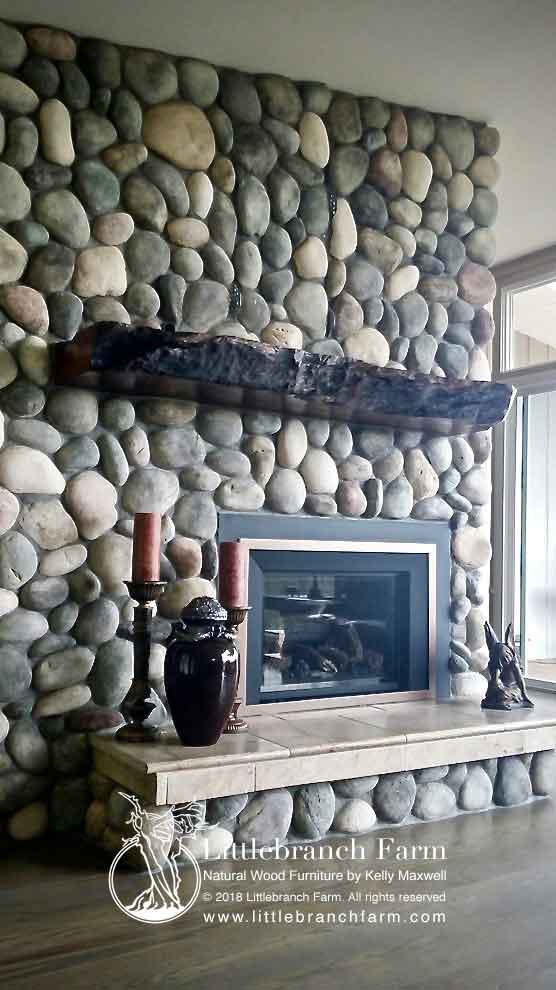 Rive er stone fireplace with live edge wood.