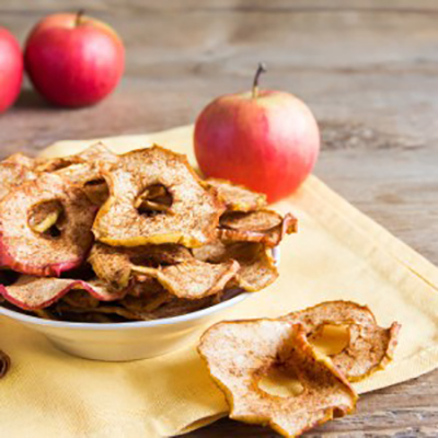 Organic apple cinnamon chips in bowl - healthy vegan vegetarian fruit snack or ingredient for cooking