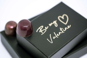 valentine's day glossy praline sitting on a black box of chocolates with embossed text in gold foil that says 'Be my valentine!'