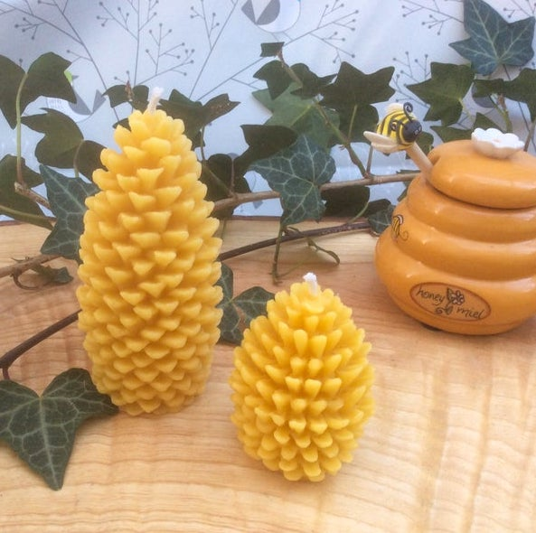 Two beeswax candles in the shape of pine cones. The wax is golden yellow in colour and the candles are standing on a wooden table surrounded by dark green ivy.