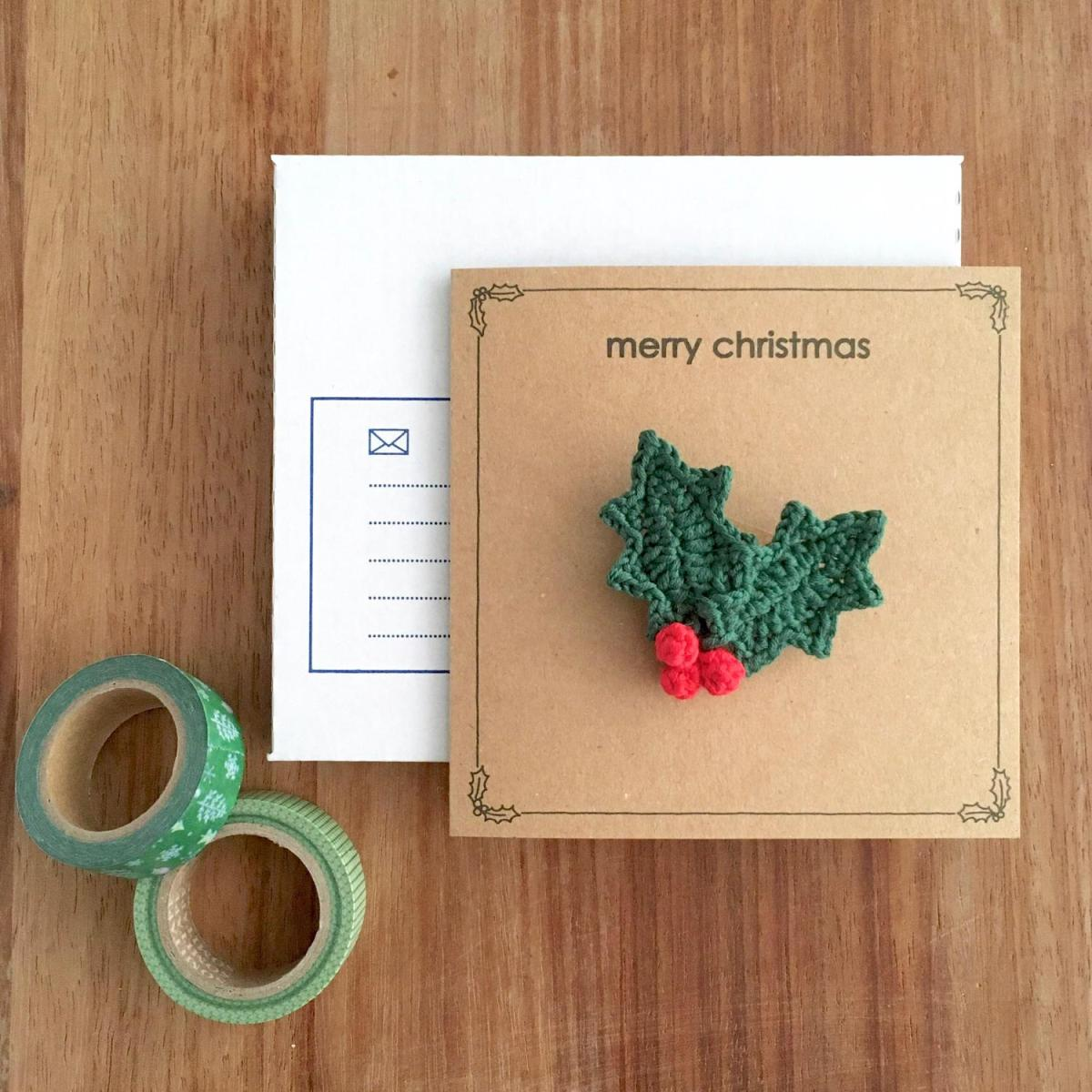 Kraft greetings card with holly sprig brooch and merry christmas message