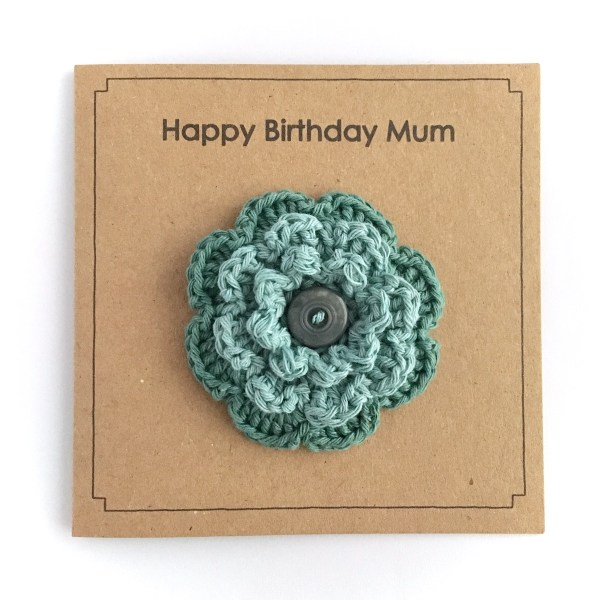 Crocheted flower brooch with button on kraft greetings card