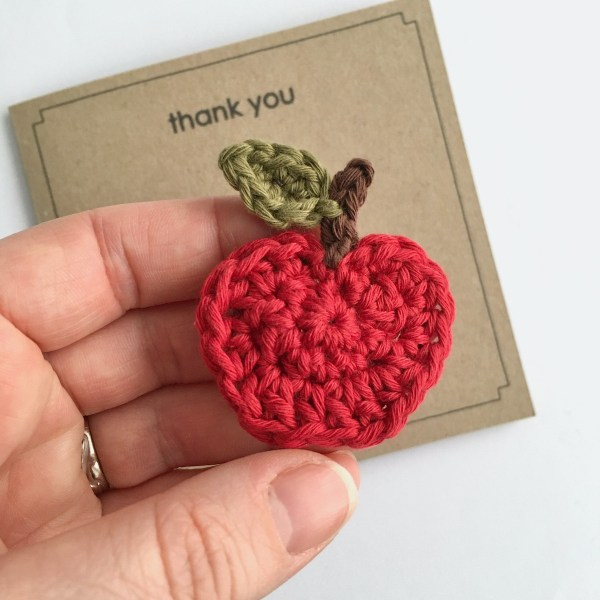 Hand holding a crocheted red apple brooch