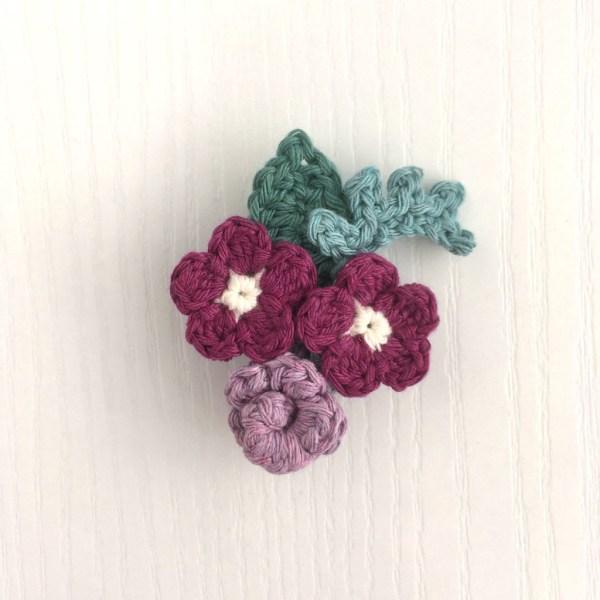 Crocheted flower bouquet brooch in purple and green