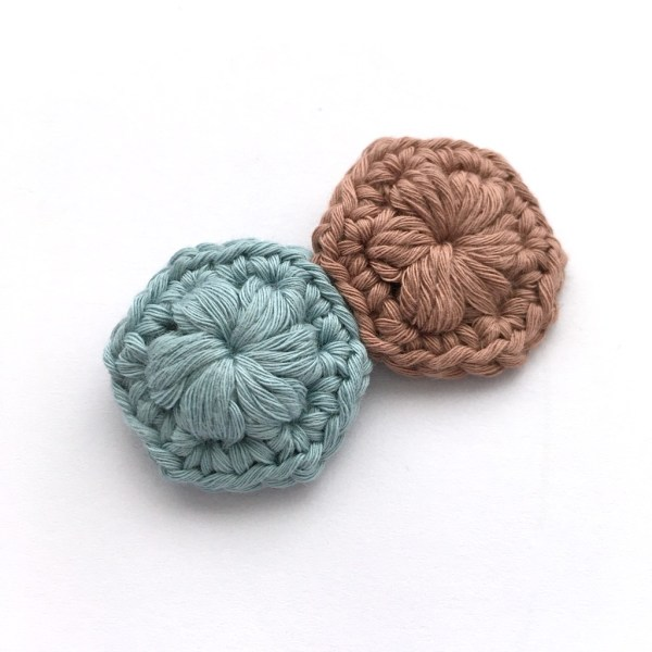 Crocheted brooch made of two hexagons in blue and brown.