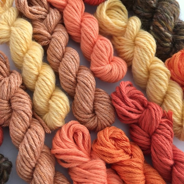 A close-up of mini yarn skeins in autumn colours