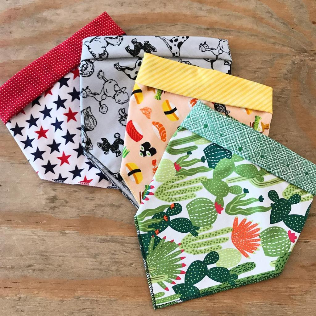 Four bandanas overlapping one another in different prints including stars, cacti, and sushi