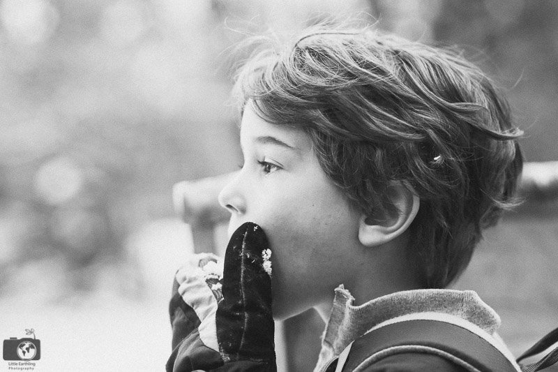 black white image of boy eating snow
