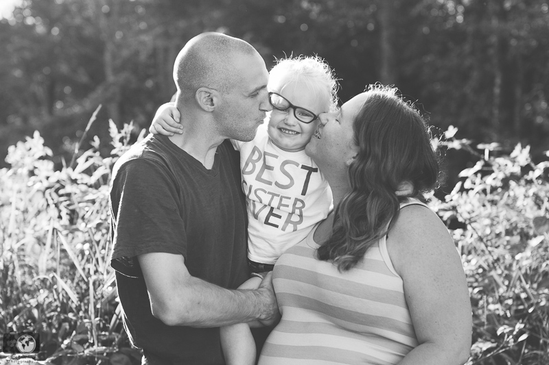 Mom and dad kissing toddler with glasses. Little Earthling Photography