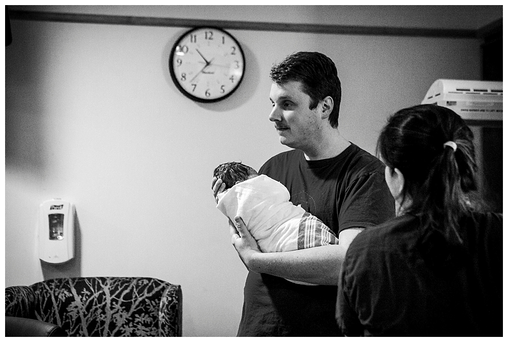 Dad holding baby after birth.