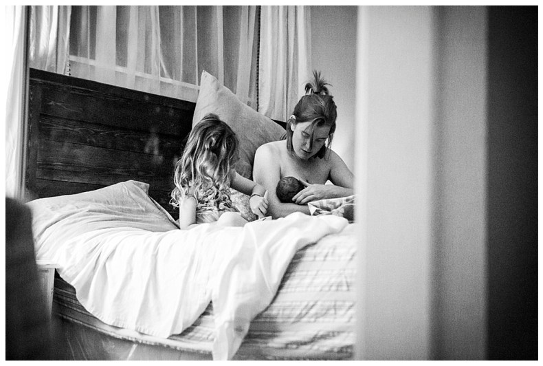 Big sister helps out her mom after watching her give birth at home. Bellingham birth photography.
