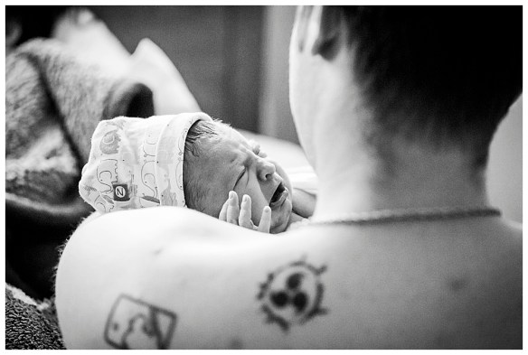 Newborn baby on dad's chest after birth. Little Earthling Photography.