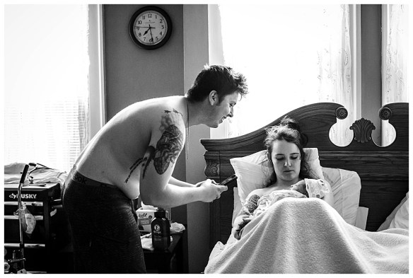 Dad taking photo of baby after birth. Little Earthling Photography.