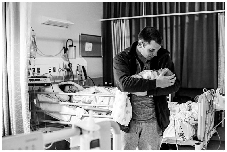Dad holding newborn in hospital.