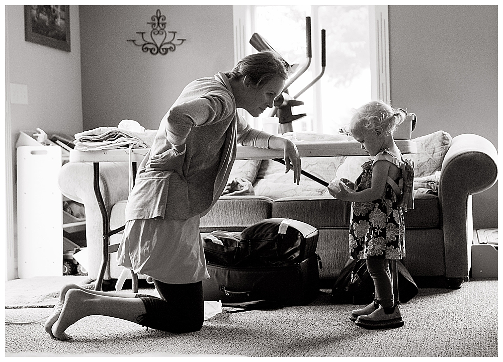 Midwife Allie Watkins, entertains a toddler during labor.