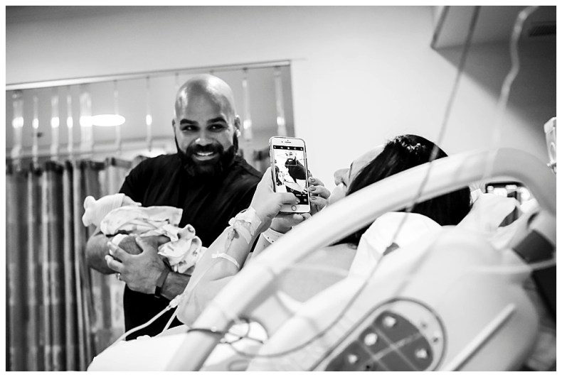 Mom taking photo of dad and baby after birth.