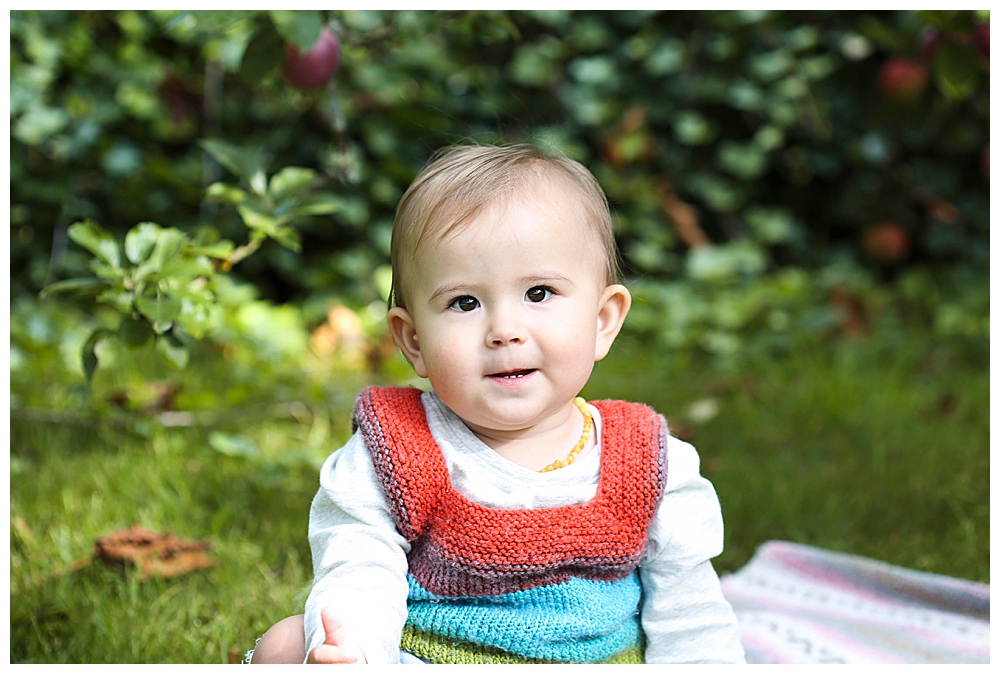 Asian baby smiling in apple orchard. Little Earthling Photography.