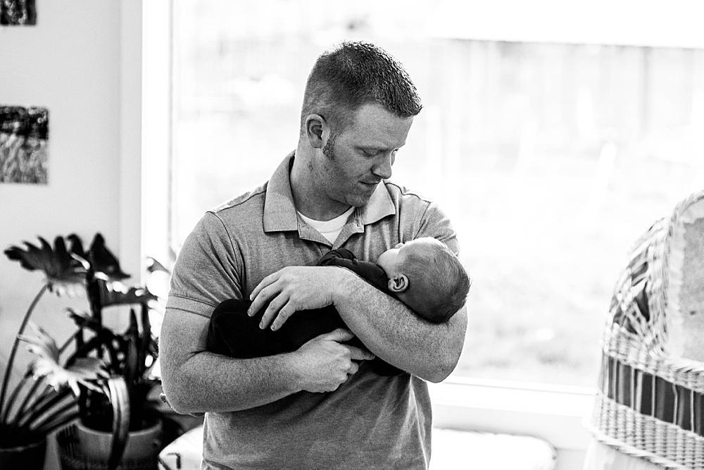 Dad cradling newborn baby. Bellingham baby photographer.