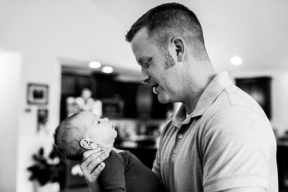 Dad starring at newborn baby during in-home session. Bellingham newborn photographer.