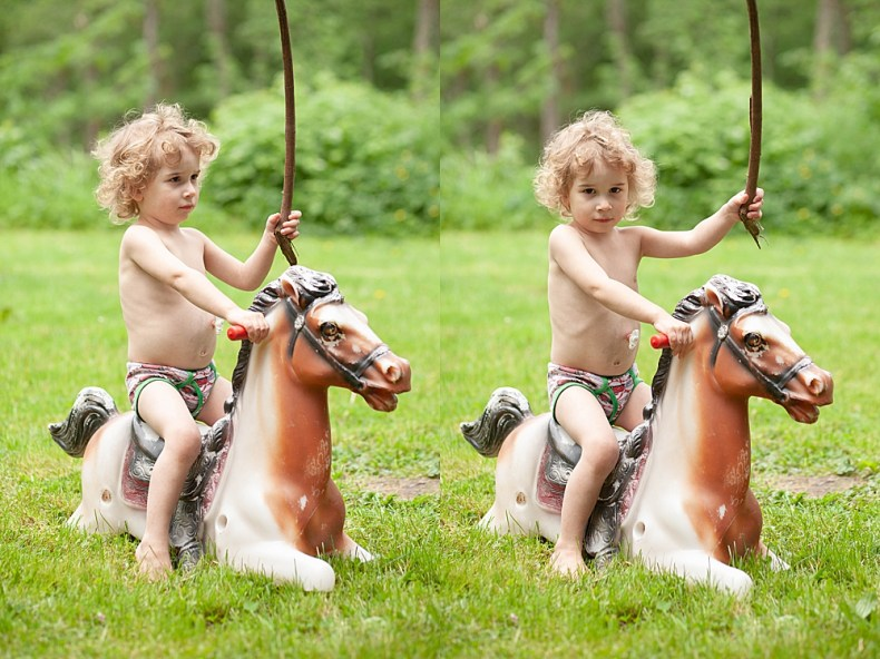 Curly haired toddler with g-tube playing on toy horse.