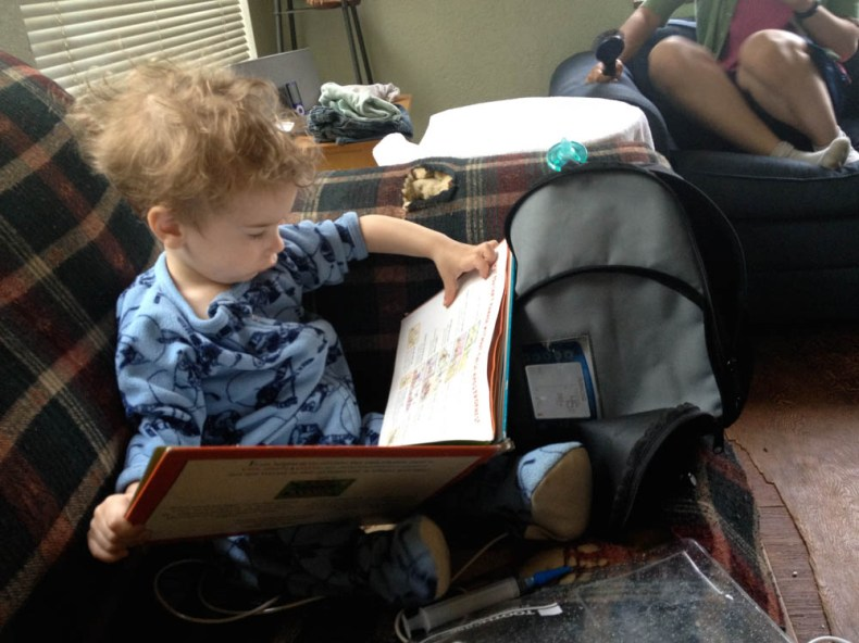 Curly-haired toddler reads book while being tube-fed.