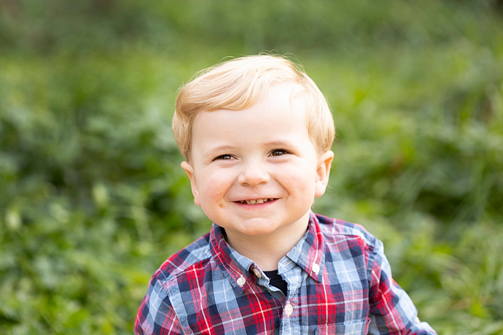 Smiling toddler during outdoor family portrait session.