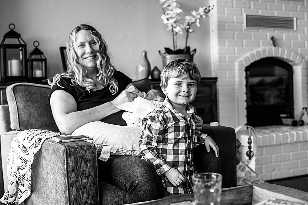 Mom, newborn, and toddler black and white lifestyle portrait.