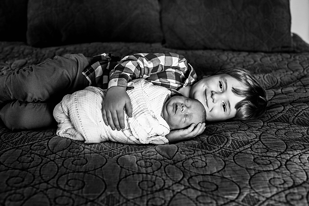 Big brother poes with baby brother during lifestyle photography session in Bellingham, WA.