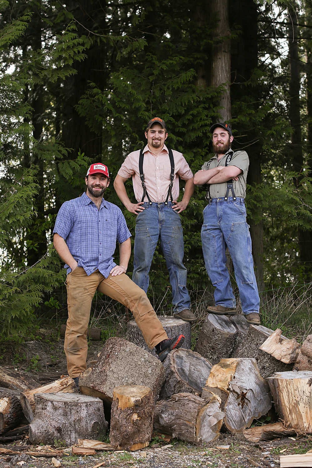 Three young men in hats and jeans posing on a pile of logs. Family photographer, Bellingham, WA