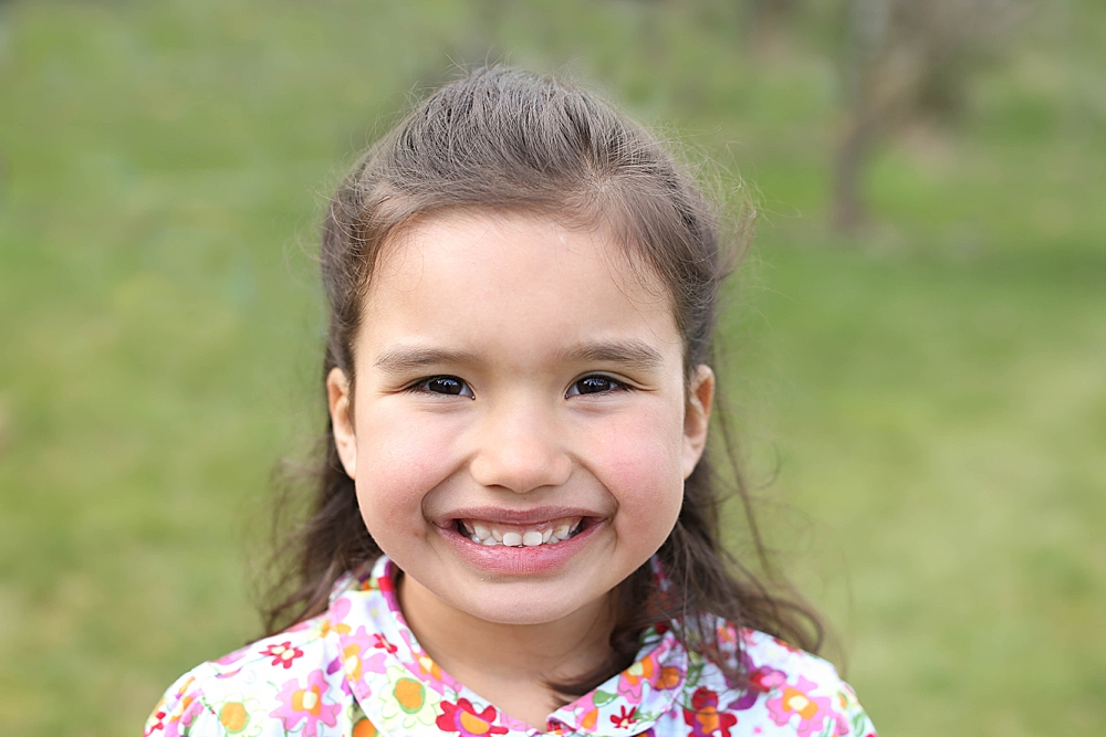 Photo of smiling girl with big brown eyes. Little Earthling Photography.